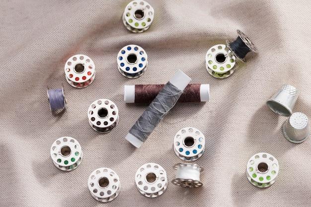 Hoge hoek van naaimachineshuttles met draadspoelen en vingerhoeden
