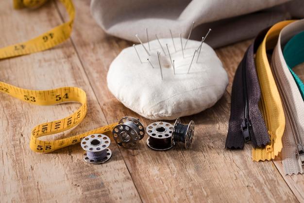 Hoge hoek van naaimachineshuttles met meetlint en ritsen