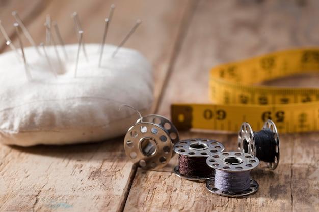 Hoge hoek van naaimachineshuttles met naalden en meetlint