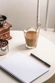 Hoge hoek van notitieboekje met koffiemolen en kop
