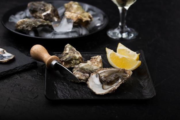 Hoge hoek van oesters op plaat met mes en citroenplakken