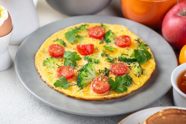 Hoge hoek van omelet in plaat met tomaten voor ontbijt