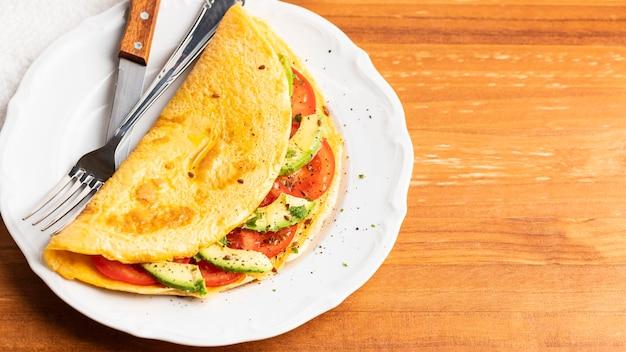 Hoge hoek van omelet met tomaten, avocado en kopieer de ruimte