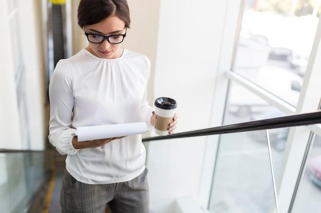 Hoge hoek van onderneemster op roltrap met koffie en blocnote