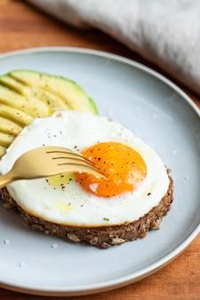 Hoge hoek van ontbijt gebakken ei op plaat met avocado en vork