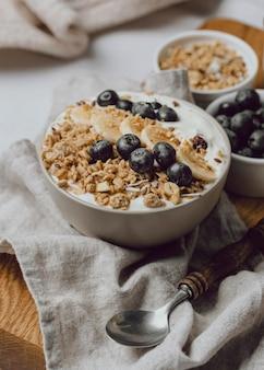 Hoge hoek van ontbijt op bed met bosbessen en ontbijtgranen