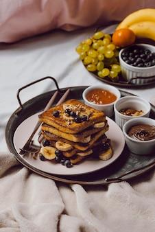 Hoge hoek van ontbijt op bed met toast en banaan
