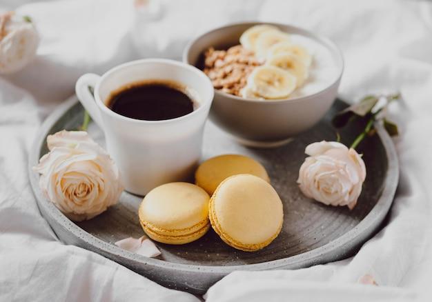 Hoge hoek van ontbijtkom met koffie en macarons