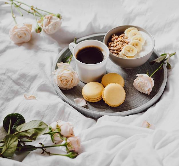 Hoge hoek van ontbijtkom met macarons en koffie