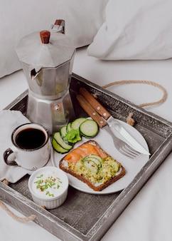 Hoge hoek van ontbijtsandwich op bed met zalm en komkommer