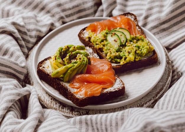 Hoge hoek van ontbijtsandwiches op bed met zalm en avocado
