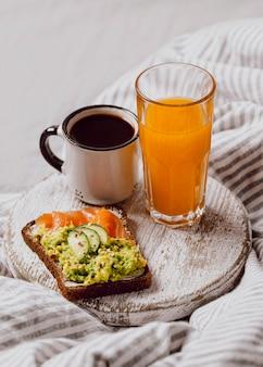 Hoge hoek van ontbijtsandwiches op bed met zalm en sap