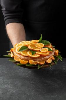 Hoge hoek van oranje cake gehouden door banketbakker