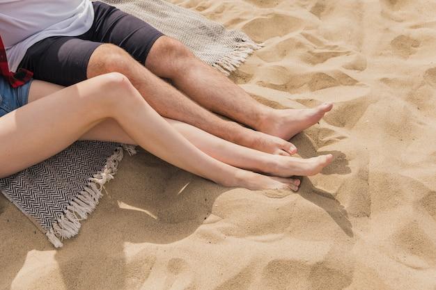 Hoge hoek van paar met voeten in zand