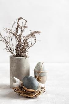 Hoge hoek van paasei in vogelnest met vaas met bloemen
