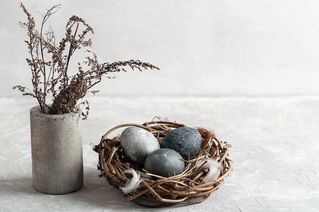 Hoge hoek van paaseieren in vogelnest met vaas met bloemen