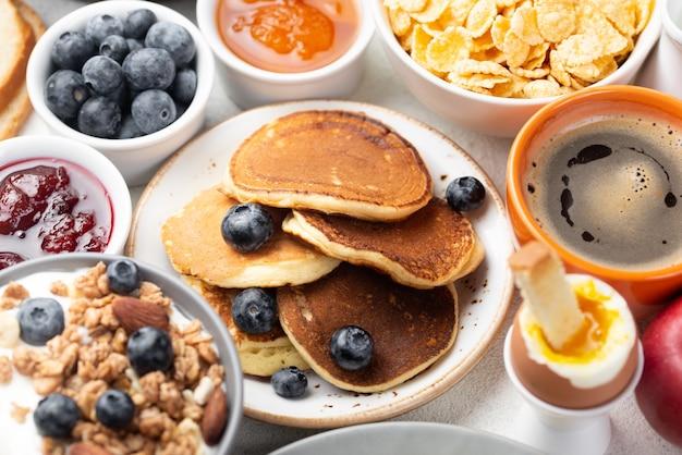 Hoge hoek van pannenkoeken met bosbessen en ontbijtgranen voor het ontbijt