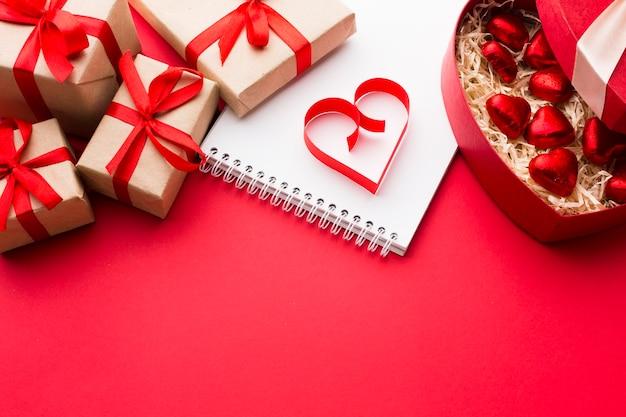Hoge hoek van papieren hartvorm met cadeautjes en snoepjes