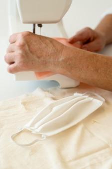 Hoge hoek van persoon die gezichtsmasker met machine naait