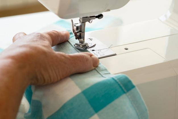 Hoge hoek van persoon die naaimachine gebruikt