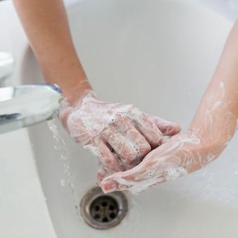 Hoge hoek van persoon handen wassen met zeep