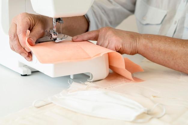 Hoge hoek van persoon naaien textiel met behulp van machine