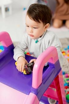 Hoge hoek van peuter spelen met speelgoed naast glijbaan