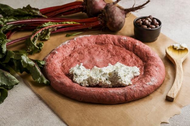 Hoge hoek van pizzadeeg met kaas en bieten
