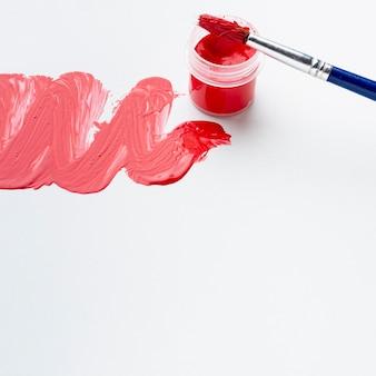 Hoge hoek van rode aquarel en penseel