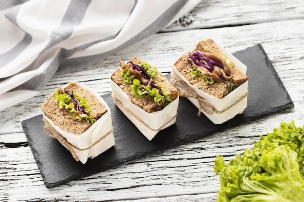 Hoge hoek van sandwiches op leisteen met salade