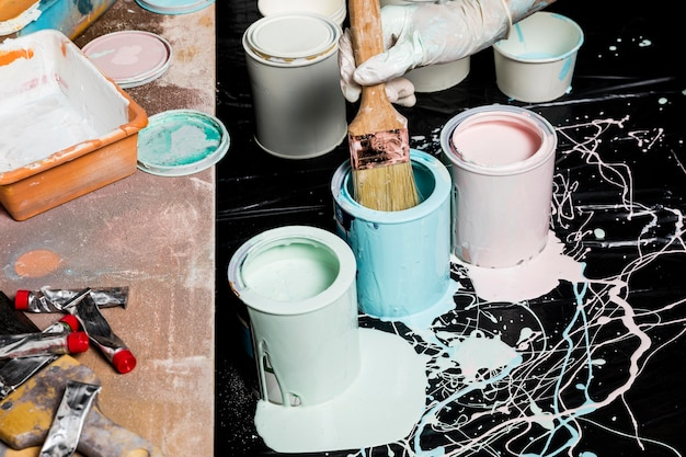 Hoge hoek van schilder met verf uit blikjes met penseel