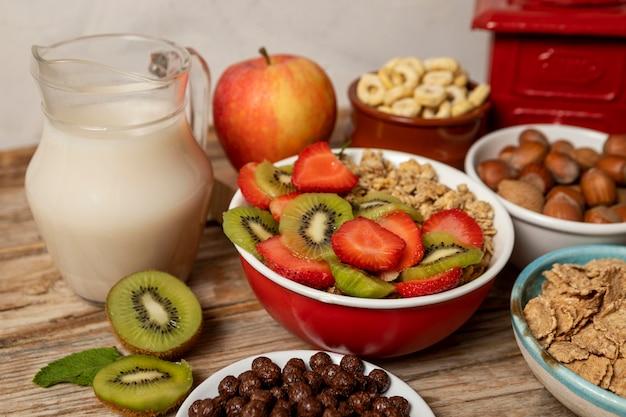 Hoge hoek van selectie van ontbijtgranen in kom met fruit en melk
