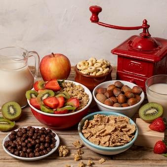 Hoge hoek van selectie van ontbijtgranen in kom met fruit