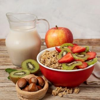 Hoge hoek van selectie van ontbijtgranen in kom met melk en fruit