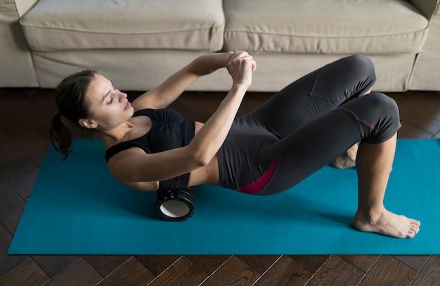 Hoge hoek van sportieve vrouw die op yogamat uitoefenen