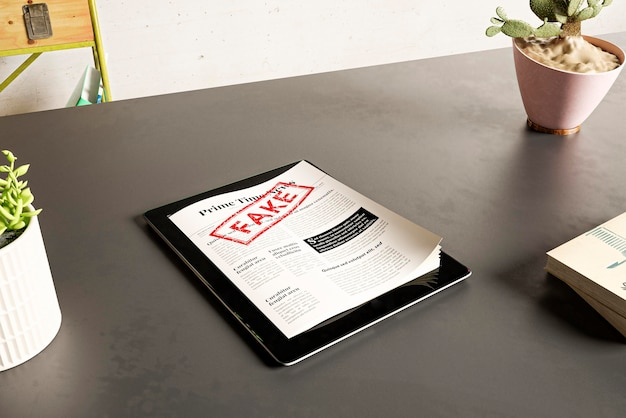 Hoge hoek van tablet met papieren en nepnieuws op tafel