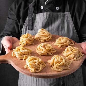 Hoge hoek van tagliatelle gehouden door chef-kok
