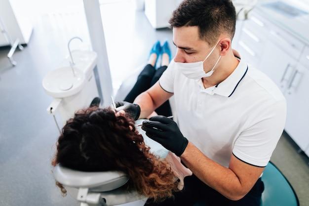 Hoge hoek van tandarts die een controle van patiënt uitvoert