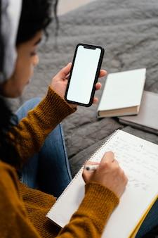 Hoge hoek van tienermeisje met behulp van smartphone voor online school