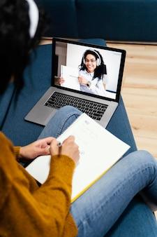 Hoge hoek van tienermeisje met koptelefoon tijdens online school