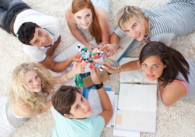 Hoge hoek van tieners die science op de vloer bestuderen