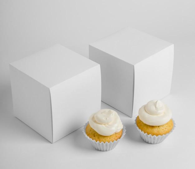 Hoge hoek van twee cupcakes met dozen