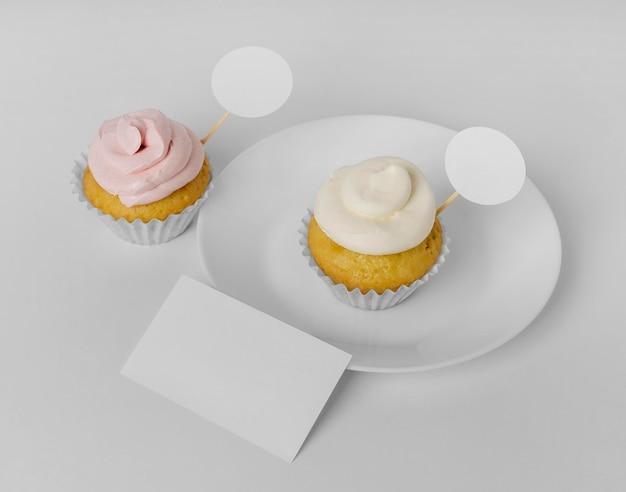 Hoge hoek van twee cupcakes met verpakking en bord