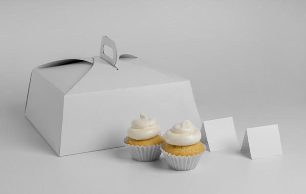 Hoge hoek van twee cupcakes met verpakkingsdoos