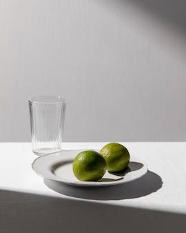 Hoge hoek van twee limoenen op plaat met helder glas