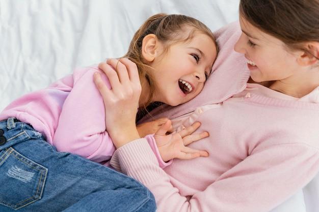 Hoge hoek van twee smileyzusters die thuis samen spelen Premium Foto