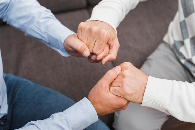 Hoge hoek van vader en zoon hand in hand