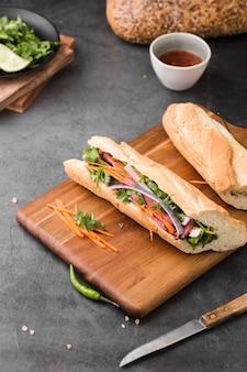 Hoge hoek van verse broodjes op hakbord met saus