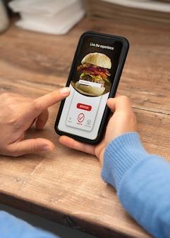 Hoge hoek van vrouw die afhaalmaaltijden bestelt op smartphone