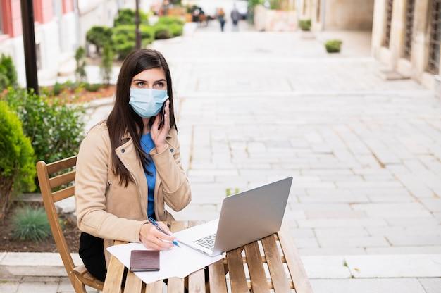 Hoge hoek van vrouw die in openlucht met laptop en smartphone werkt